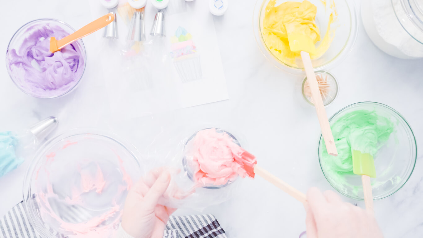 Preparing piping bags with colorful buttercream frosting to decorate unicorn theme vanilla cupcakes