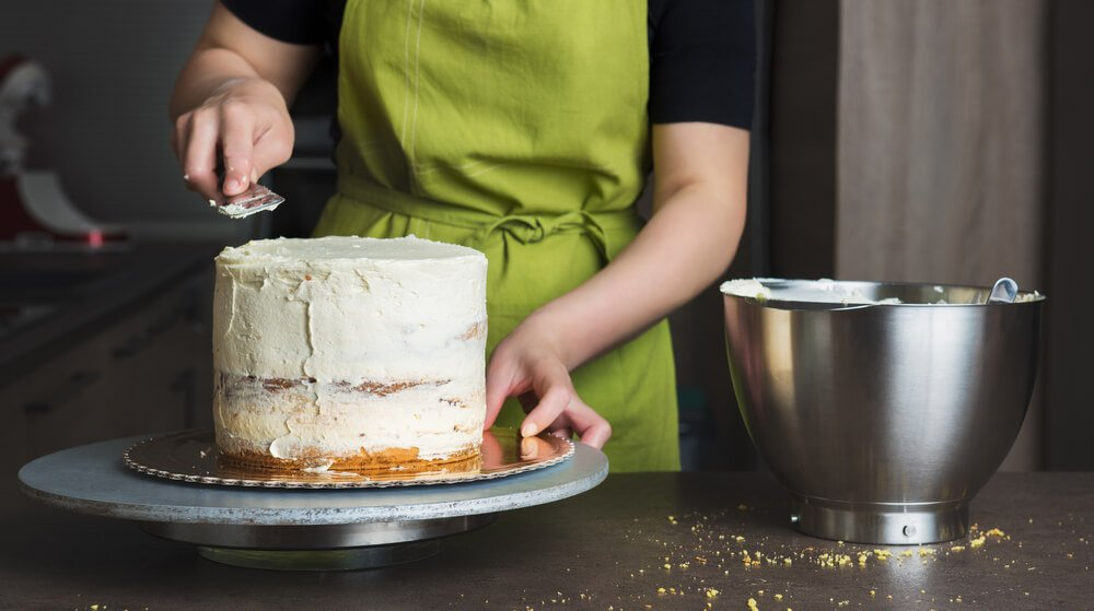 Unrecognisable Woman Decorating a Delicious Layered Sponge Cake With Icing Cream.