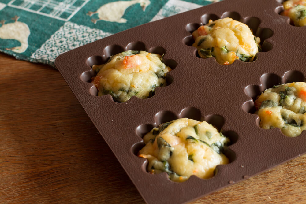 Muffin With Salmon, Spinach and Cheese in Silicone Brown Bakeware on Green Tablecloth With Gooses.