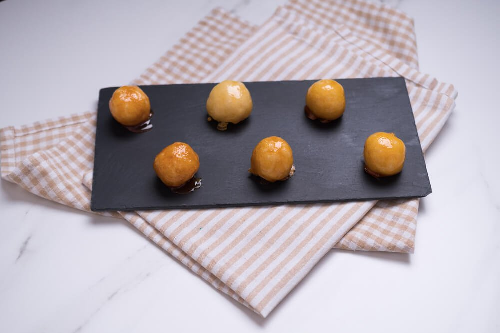 Coquitos Coconut Balls With Caramel on Black Slate on Squared Rag on White Marble