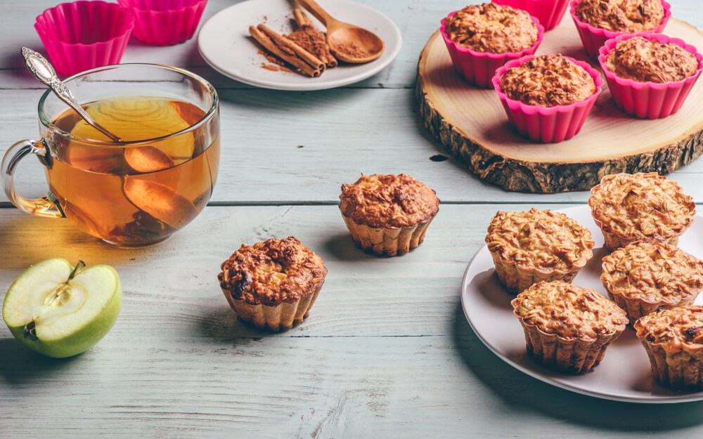 Cooked Oatmeal Muffins With Apple and Cup of Green Tea Over Light Wooden Background.